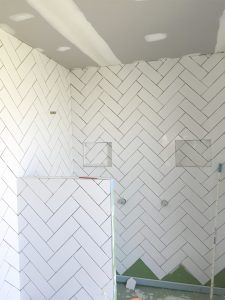 White subway tiles Ensiute in herringbone pattern