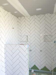 White subway tiles Ensiute in herringbone pattern